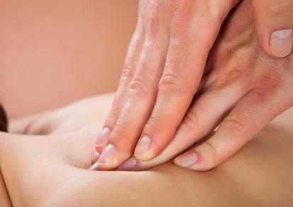 Closeup of male therapist massaging female customer's back at beauty spa
